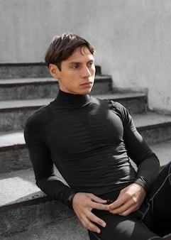 Человек в спортивной одежде позирует на лестнице