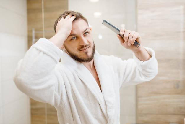 バスローブを着た男がバスルームで髪をとかす