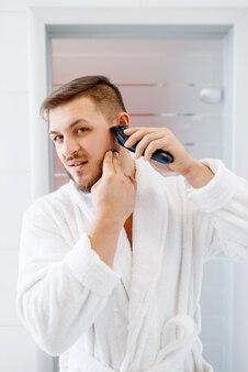 목욕 가운을 입은 남자는 일상적인 아침 위생을 위해 욕실에서 전기 면도기로 수염을 면도합니다.