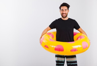 Man in beachwear with floating tube around his waist close up view