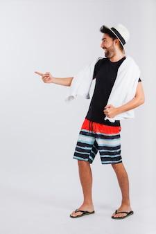 Человек в пляжной одежде с полотенцем, указывающим куда-то