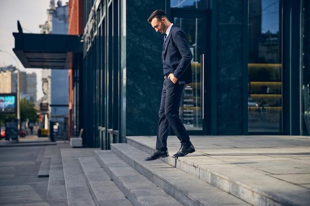 Мужчина в красивой официальной одежде выходит из офиса и радостно спускается по лестнице