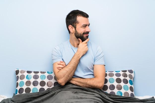 Мужчина в постели смотрит в сторону