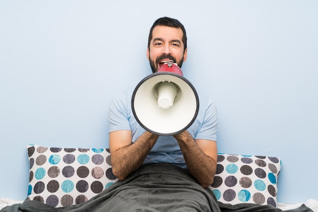 Мужчина в постели кричит через мегафон