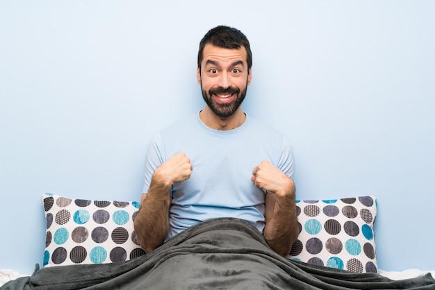 Человек в постели с удивленным выражением лица