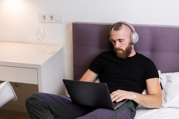 침대에 침실에있는 남자는 노트북 앞에서 잠 들었다.