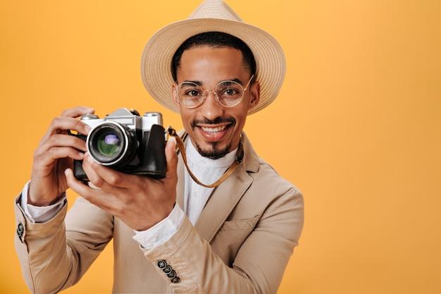 ベージュの帽子の男はオレンジ色の壁にレトロなカメラを保持しています