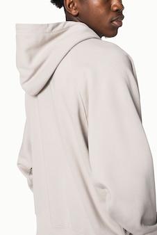 Мужчина в бежевой толстовке с капюшоном в зимней молодежной одежде.