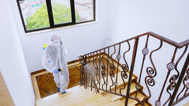Мужчина в костюме биологической опасности распыляет химические вещества на блочной лестнице против covid-19.
