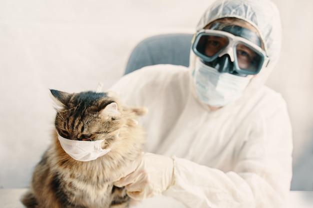 バイオハザードスーツと子猫の男は保護マスクでフェイスシールド猫を着用します