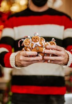 黒と赤の冬のセーターと手作りのおもちゃのクッキーの束を保持している医療マスクの男