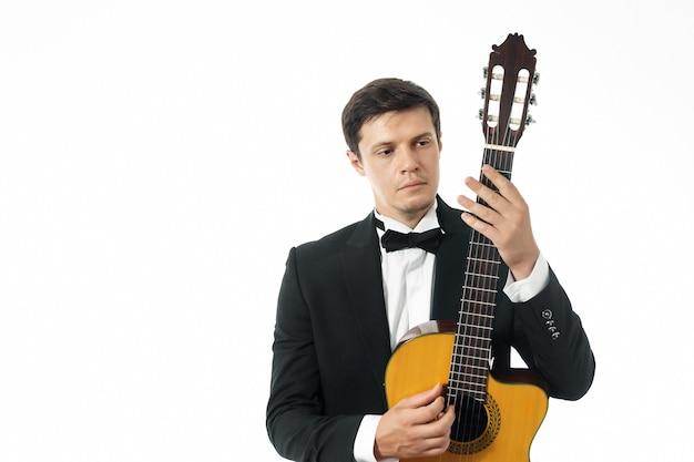 클래식 기타와 함께 포즈를 취하고 클래식 기타의 목을 바라보는 검은색 클래식 정장을 입은 남자
