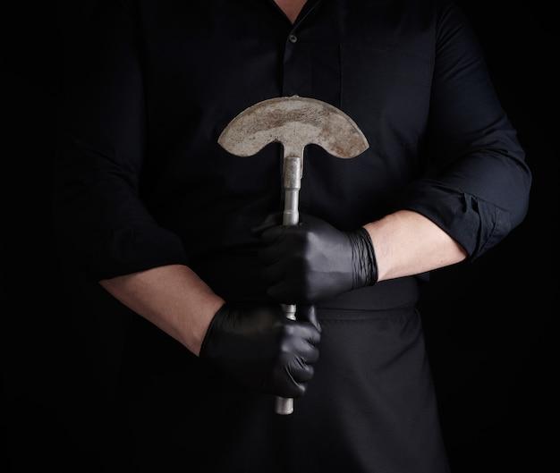 黒い服を着た男、ラテックス手袋はヴィンテージの金属製の斧ナイフを保持