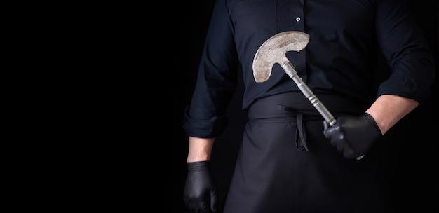 Мужчина в черной одежде, латексных перчатках держит старинный металлический топор-нож