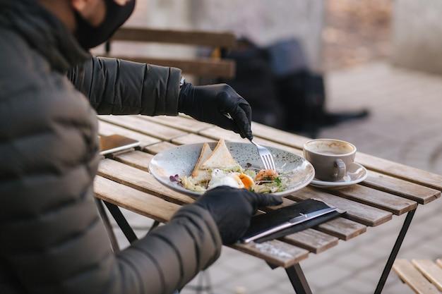 カフェに座ってビーガンサラダを食べる準備をしている黒いフェイスマスクの男。検疫カフェのコンセプト。 covid-19