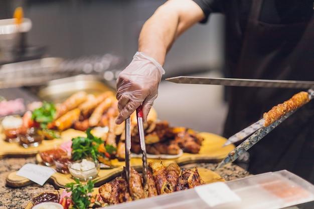 검은 장갑에 남자는 흰 접시에 음식 주걱으로 양고기를 넣어. 양고기의 맛있는 조리 된 갈색 고기.