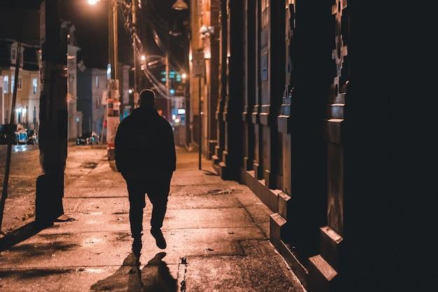 Человек в черном балахоне, ходить по тротуару в ночное время