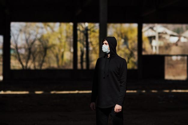 Мужчина в черной толстовке с капюшоном с маской, чтобы защитить его от коронавируса