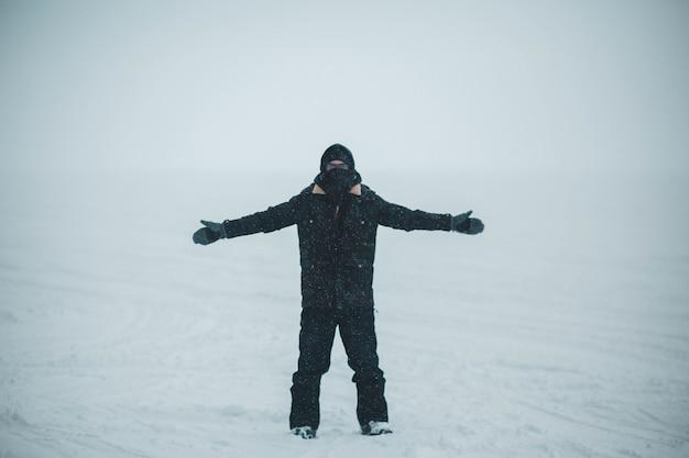 Человек в черной куртке и брюках стоит на заснеженной земле