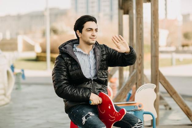 공원의 유치한 회전 목마에 앉아 인사하거나 손짓으로 누군가에게 전화하는 검은 재킷을 입은 남자. 고품질 사진