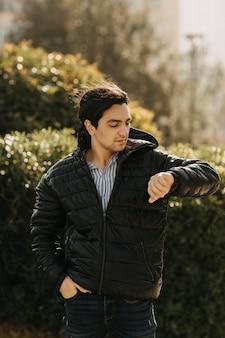 공원에 서서 그의 시간을 확인하는 검은 재킷을 입은 남자. 고품질 사진