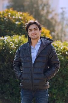 공원에 서서 누군가를 기다리는 검은 재킷을 입은 남자. 고품질 사진