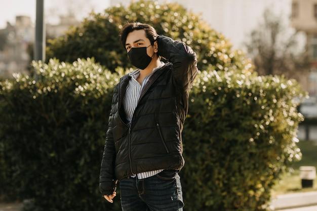 검은 가죽 재킷과 공원에서 산책하는 검은 얼굴 마스크에 남자. 고품질 사진
