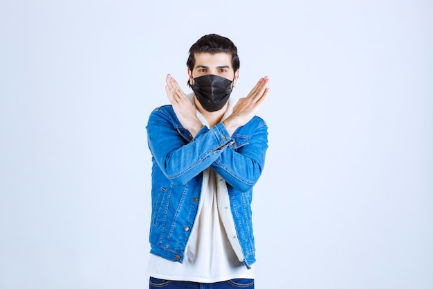 바이러스에 정지 신호를주는 검은 마스크에 남자.
