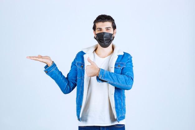 楽しさのサインを示し、気分が良い黒いマスクの男。
