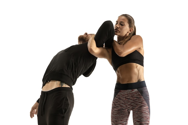 Мужчина в черном костюме и спортивная женщина борются на белой стене студии