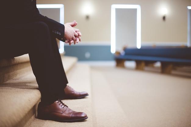 검은 바지를 입은 남자와 갈색 가죽 레이스 업 신발 한 켤레가 방 안의 갈색 카펫 계단에 앉아있다.