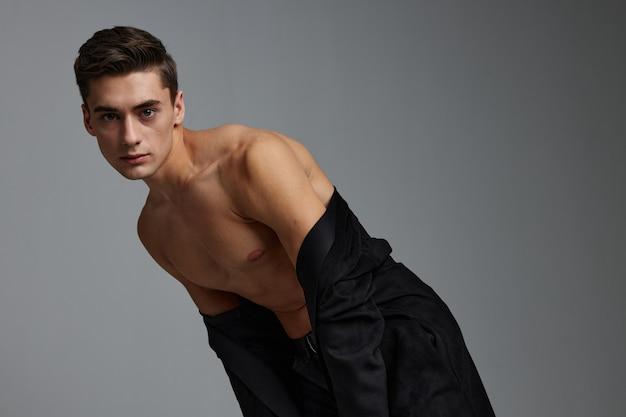 Мужчина в черной рубашке обнажил плечи, основываясь на эмоциях модельного образа жизни.