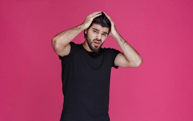 黒のシャツを着た男が頭を覆い、頭痛を感じる