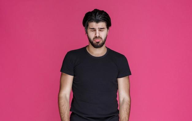 뭔가에 대해 부정적인 느낌과 실망감을 느끼는 검은 셔츠를 입은 남자