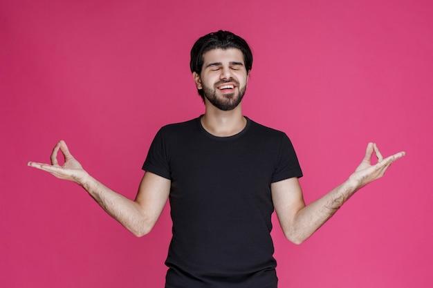 검은 셔츠를 입은 남자는 무언가에 대해 긍정적 인 느낌을 갖고 그것을 즐깁니다.