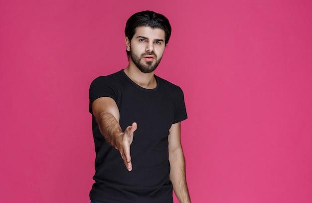 黒のシャツを着た男が手を差し伸べて誰かに挨拶し、手を振る。