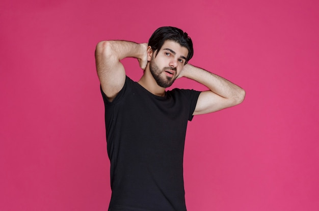 검은 셔츠를 입은 남자는 편안하고 시원하며 들떠 보입니다.