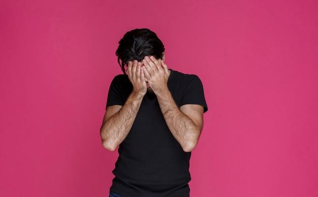 黒のシャツを着た男は、何かにショックを受けて疲れているように見えます