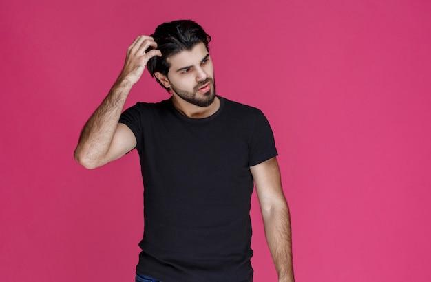 黒のシャツを着た男は、思慮深く、混乱し、躊躇しているように見えます。