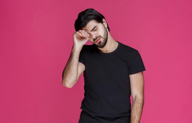 검은 셔츠를 입은 남자는 피곤하고 지루하며 졸려 보입니다.