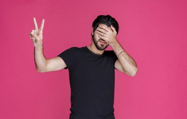 Человек в черной рубашке делает знак мира рукой