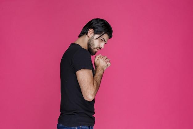 何かを祈って夢を見ている黒いシャツを着た男