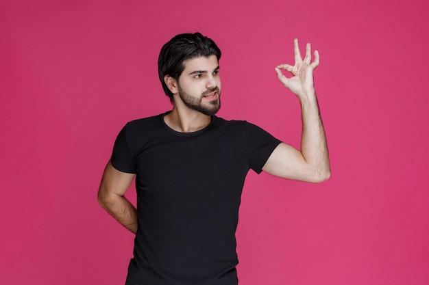 Мужчина в черной рубашке показывает, что ему что-то полностью нравится