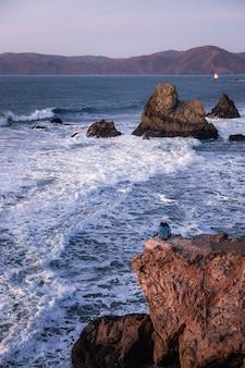 Человек в черной рубашке сидит на коричневой скале у моря в дневное время