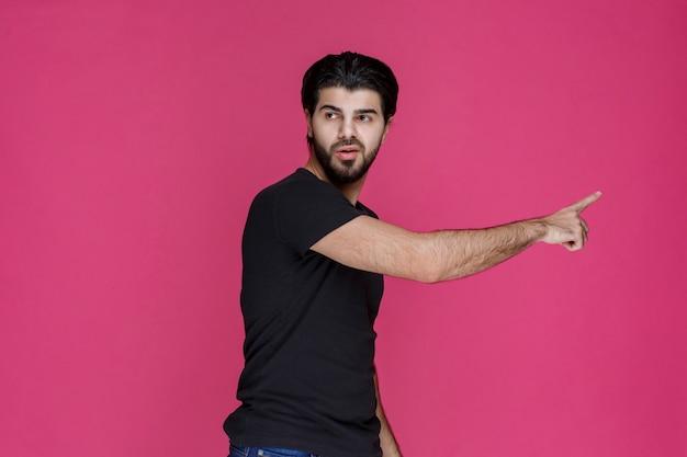 혼란스러운 방식으로 무언가를 가리 키거나 방향을 보여주는 수염을 가진 검은 셔츠에 남자