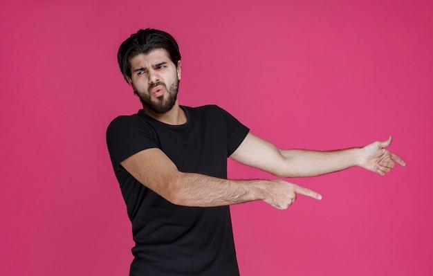 혼란스러운 방식으로 무언가를 가리 키거나 방향을 보여주는 수염을 가진 검은 셔츠를 입은 남자.