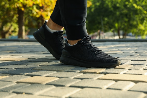 Человек в черных кроссовках и спортивных штанах бежит в парке
