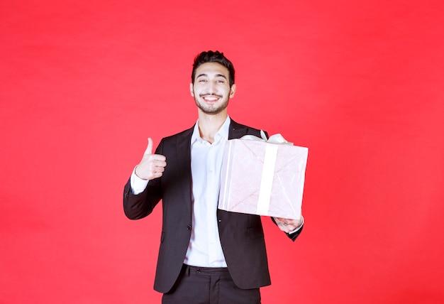Человек в черном костюме держит фиолетовую подарочную коробку и показывает положительный знак рукой.