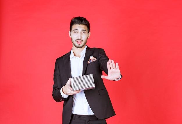 Человек в черном костюме держит серебряную подарочную коробку и что-то останавливает.