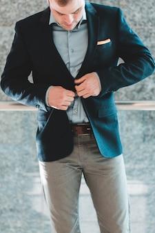 Человек в черном пиджаке и серых брюках